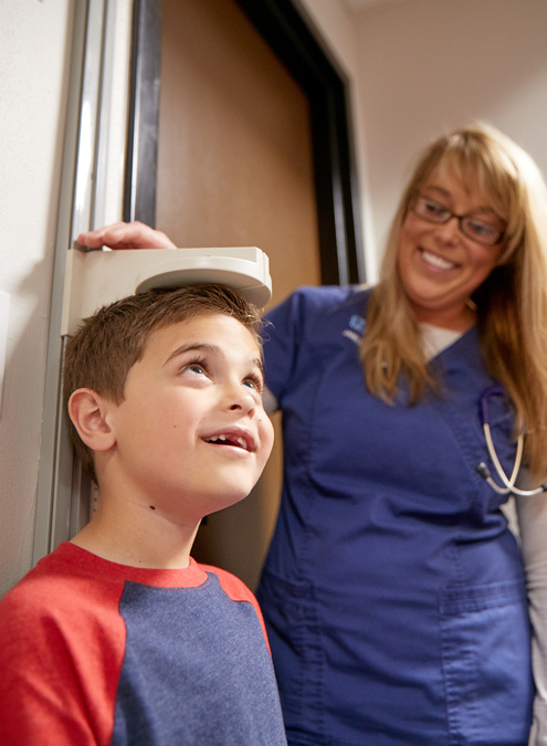 Nurse taking height on a child patient