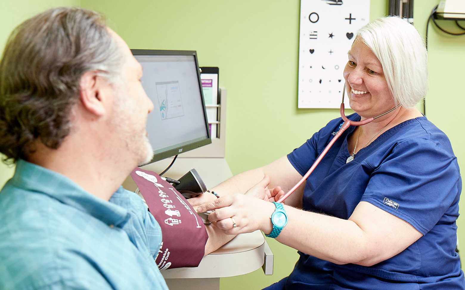 Nurse taking the blood pressure of a patient in a QuadMed onsite health center