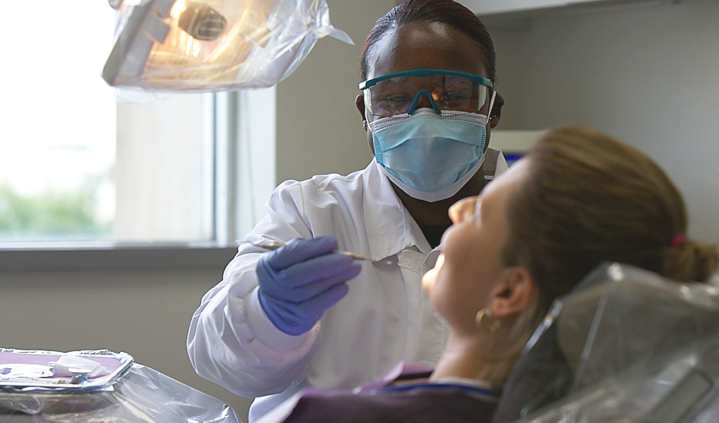 Dental assistant looking at patients mouth
